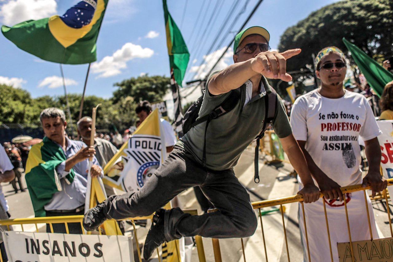 Manifestante pula cerca que divide protesto contra e a favor do presidente Lula em frente ao Fórum da Barra Funda. Foto: São Paulo