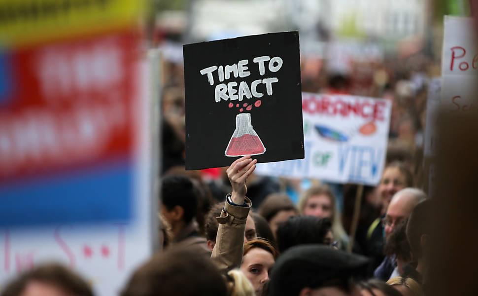 """""""Hora de reagir"""", brinca cartaz de participante da Marcha pela Ciência em Londres, do lado de fora do Museu de Ciência da cidade. Foto: Daniel Leal-Olivas/AFP"""