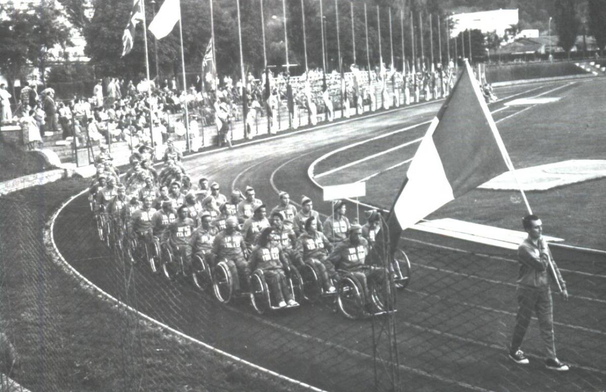 Imagem antiga, em preto e branco, que mostra uma pista de atletismo com várias pessoas sobre cadeira de rodas, em fileiras, seguindo um homem que caminha com a bandeira da Itália.