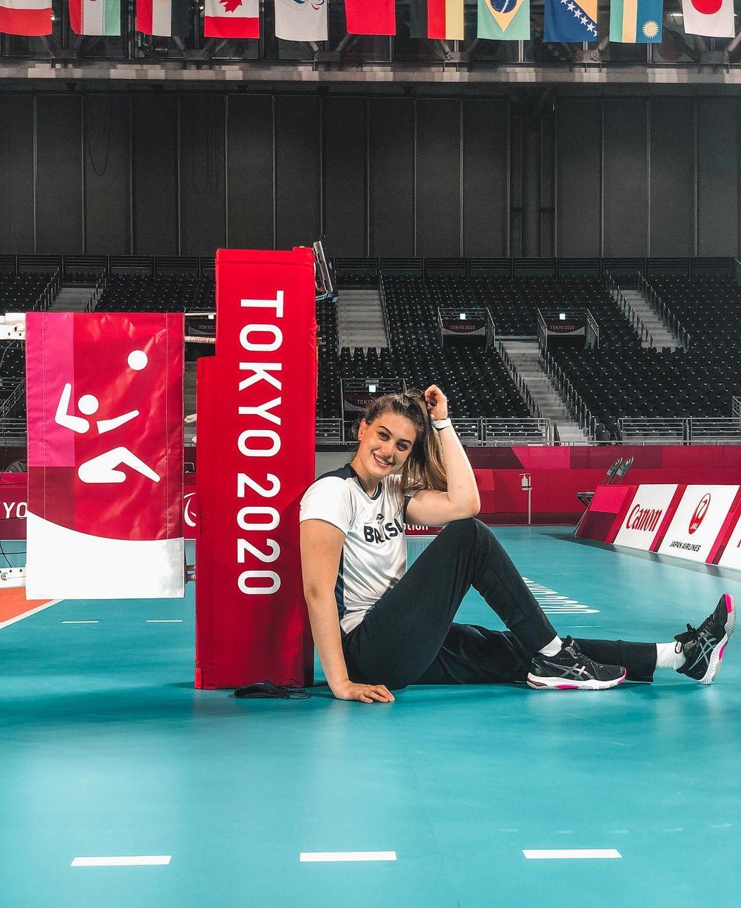 Luiza está sentada em quadra de volei, sorrindo para a cânera e encostada em uma placa escrita Tokyo 2020
