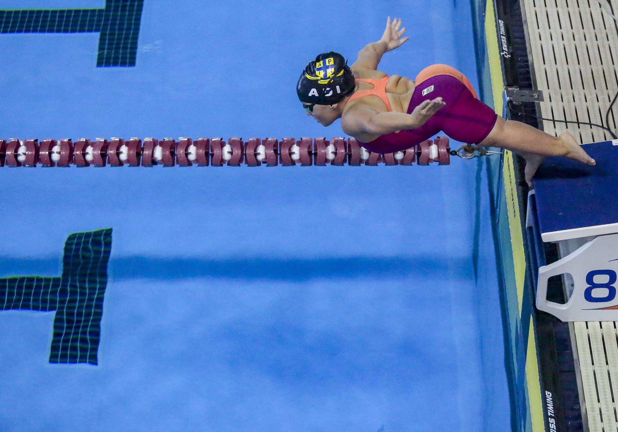 Foto da pequena Esthe vista do alto, pulando em direção à piscina. Ela uma um maiô laranja e roxo a touca de natação.