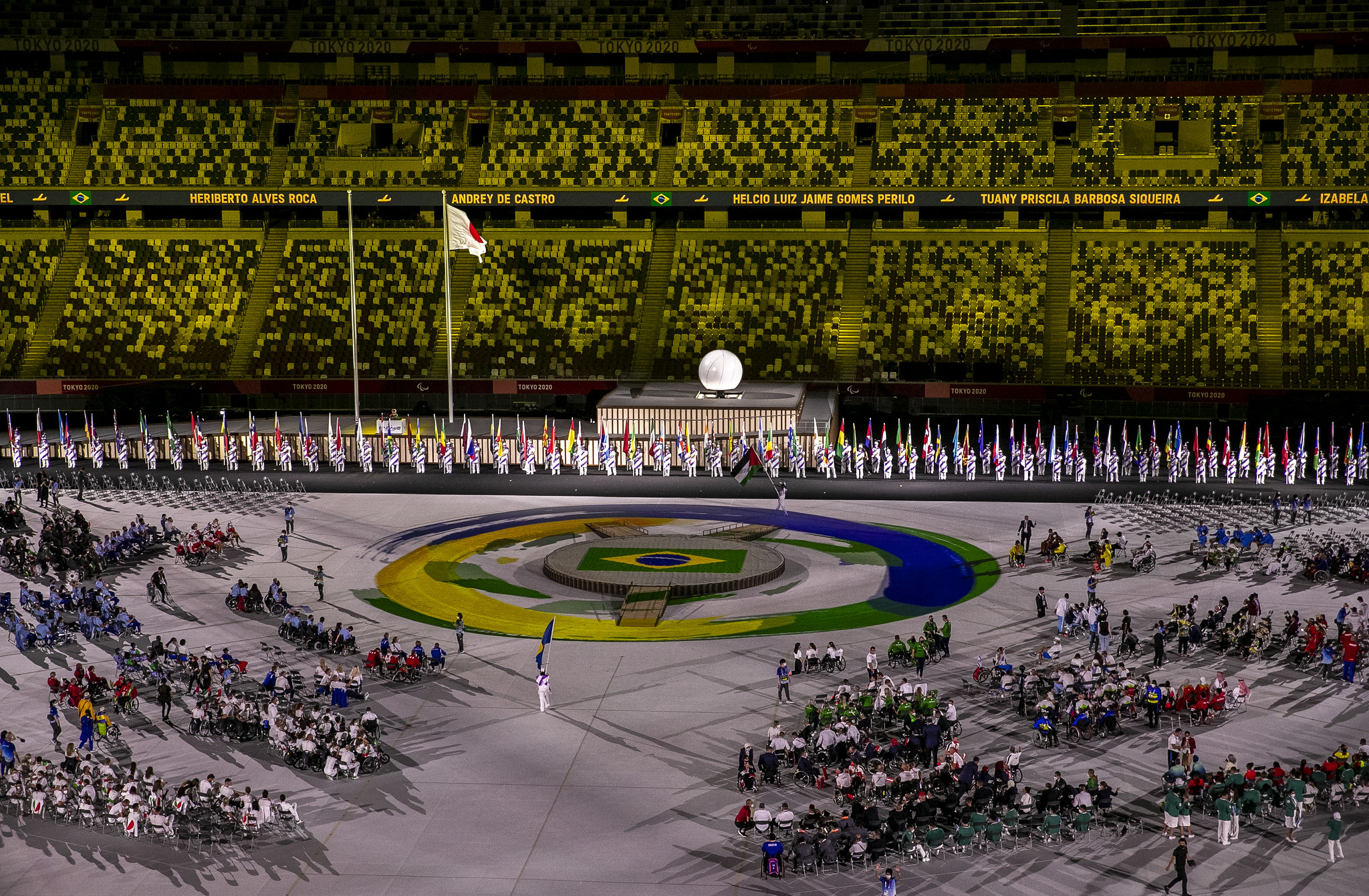 A foto foi feita em uma parte da cerimônia de abertura dos Jogos Paralímpicos de Tóquio. Há um tablado central no estádio com a bandeira e as cores do Brasil. Diversos atletas paralímpicos aparecem distribuídos no local.