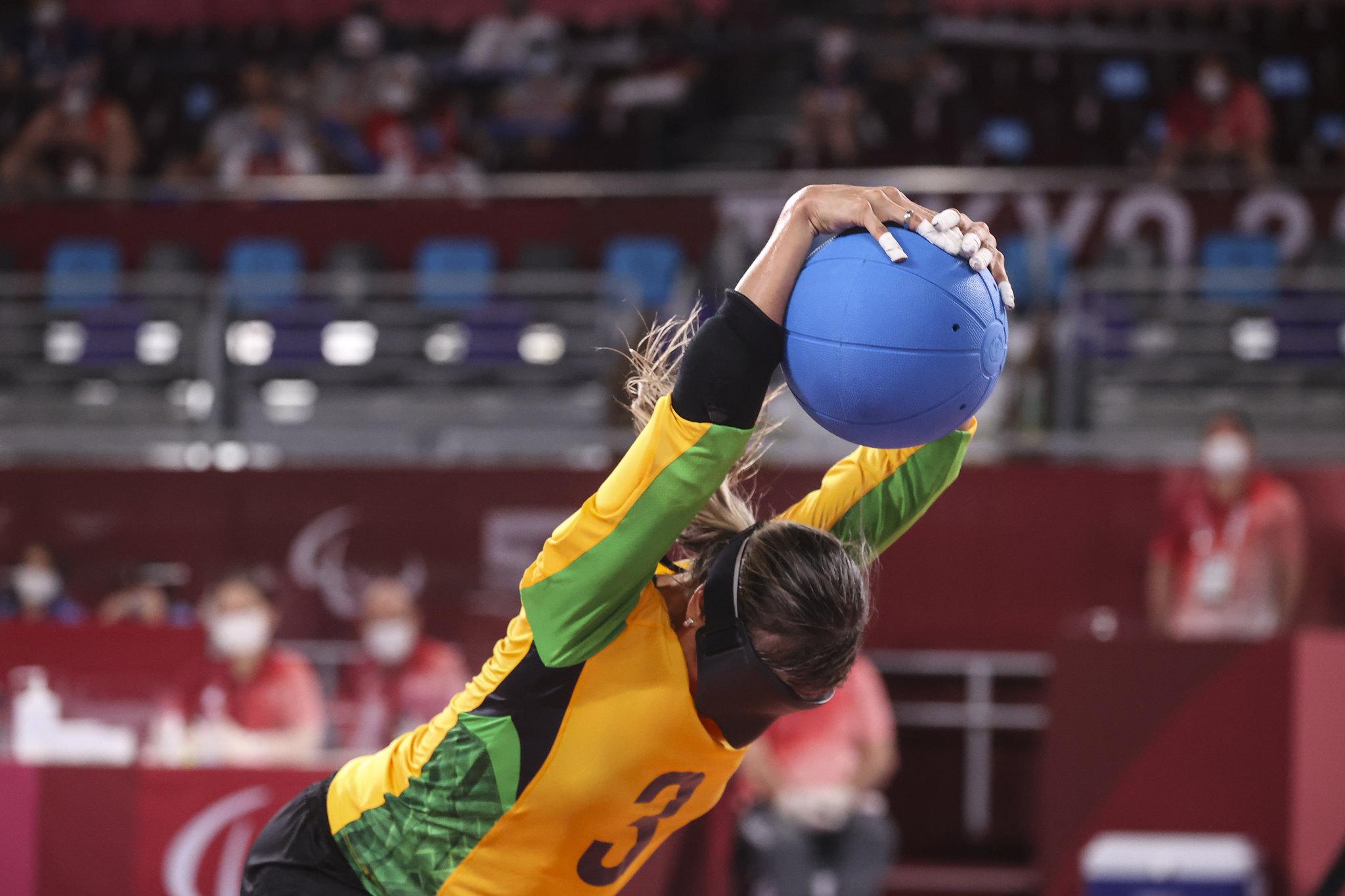 Foto de uma atleta durante o jogo de Golbol, ela usa a venda preta e agarra uma bola azuul, com os braços levantados.