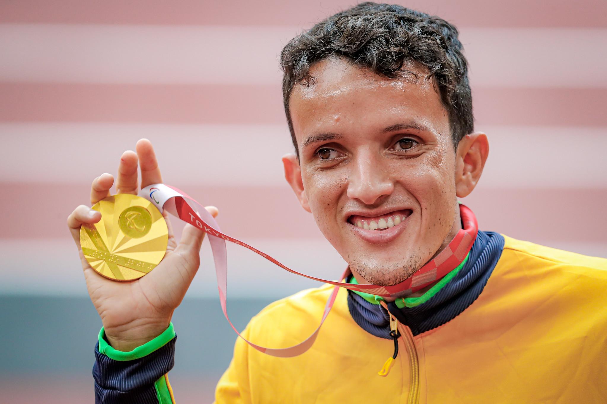 Imagem de perfil do atleta Yeltsin, um homem branco, sorridente, segurando a medalha de ouro com sua mão direita.