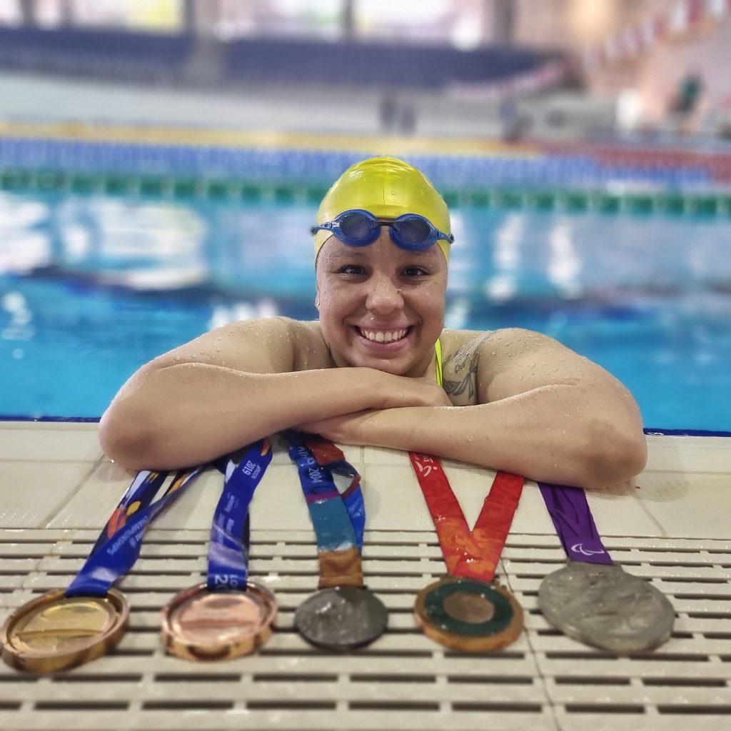 foto perfil de Edênia posando sobre a borda de uma piscina. Em frente a ela, estão 5 medalhas de competições diferentes: uma de ouro, duas de bronze e duas de prata.