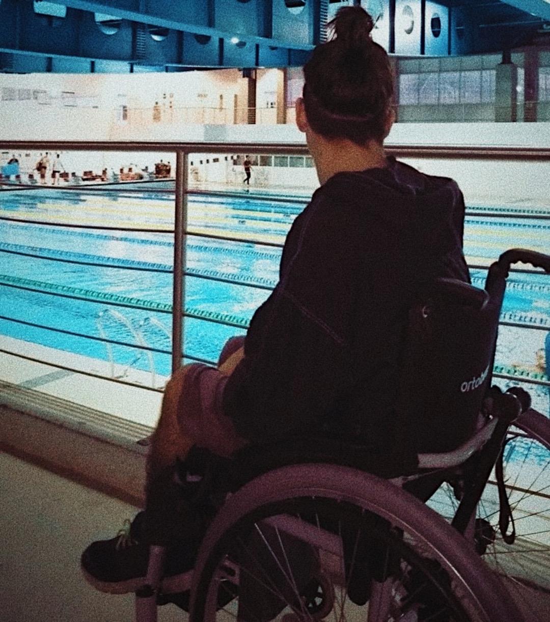 Está foto foi tirada no Centro Paralímpico de São Paulo, Tato é um menino branco e ele veste um agasalho preto. Ele está com o seu cabelo preso e a lateral toda de seu cabelo raspada, o mesmo veste uma bermuda bege e um tênis azul e branco com o cordão verde-florescente. Ele está sentado em sua cadeira de rodas (Fly) preta e cinza, ele está de costas para a foto em uma arquibancada olhando a piscina e alguns atletas treinando. A estrutura superior do ginásio é pintada toda em azul escuro.