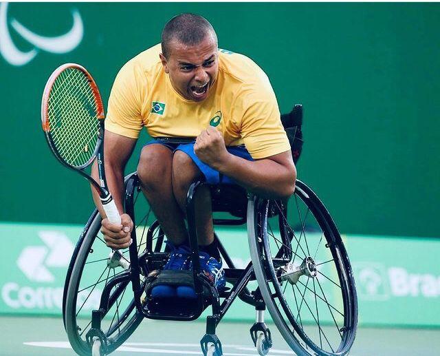 Fotografia do tenista Rafael Medeiros em que aparece na cadeira de rodas com o uniforme verde, amarelo e azul do Brasil e uma raquete na mão esquerda.