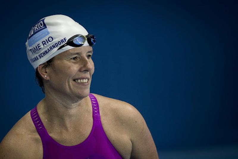 Foto de perfil de Susana sorrindo., uma mulher branca de 53 anos. Ela usa uma touca de natação branca.