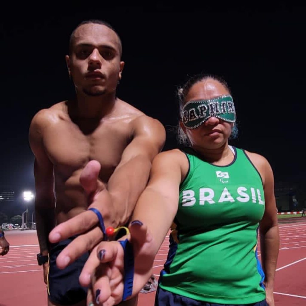 Em uma pista de corrida, Mateus e Jhulia, lado a lado, encostam os braços que estão estendidos e presos por uma guia. Mateus está sem camisa e Jhulia com uniforme verde escrito Brasil e venda verde escrito Saphir. Os dois estão sérios.