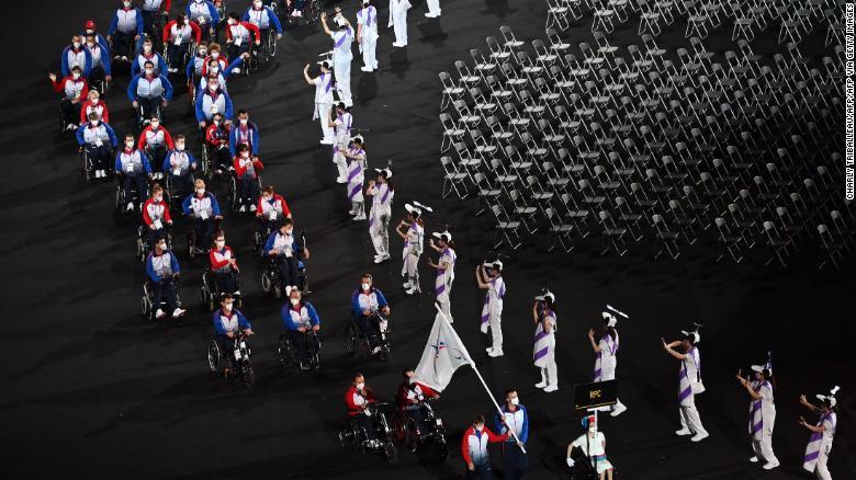 Foto da cerimônia de abertura dos jogos paralímpicos de Tóquio, quando a delegação russa desfila com diversos participantes em cadeiras de rodas. Na lateral à direita aparece uma série de cadeiras vazias.