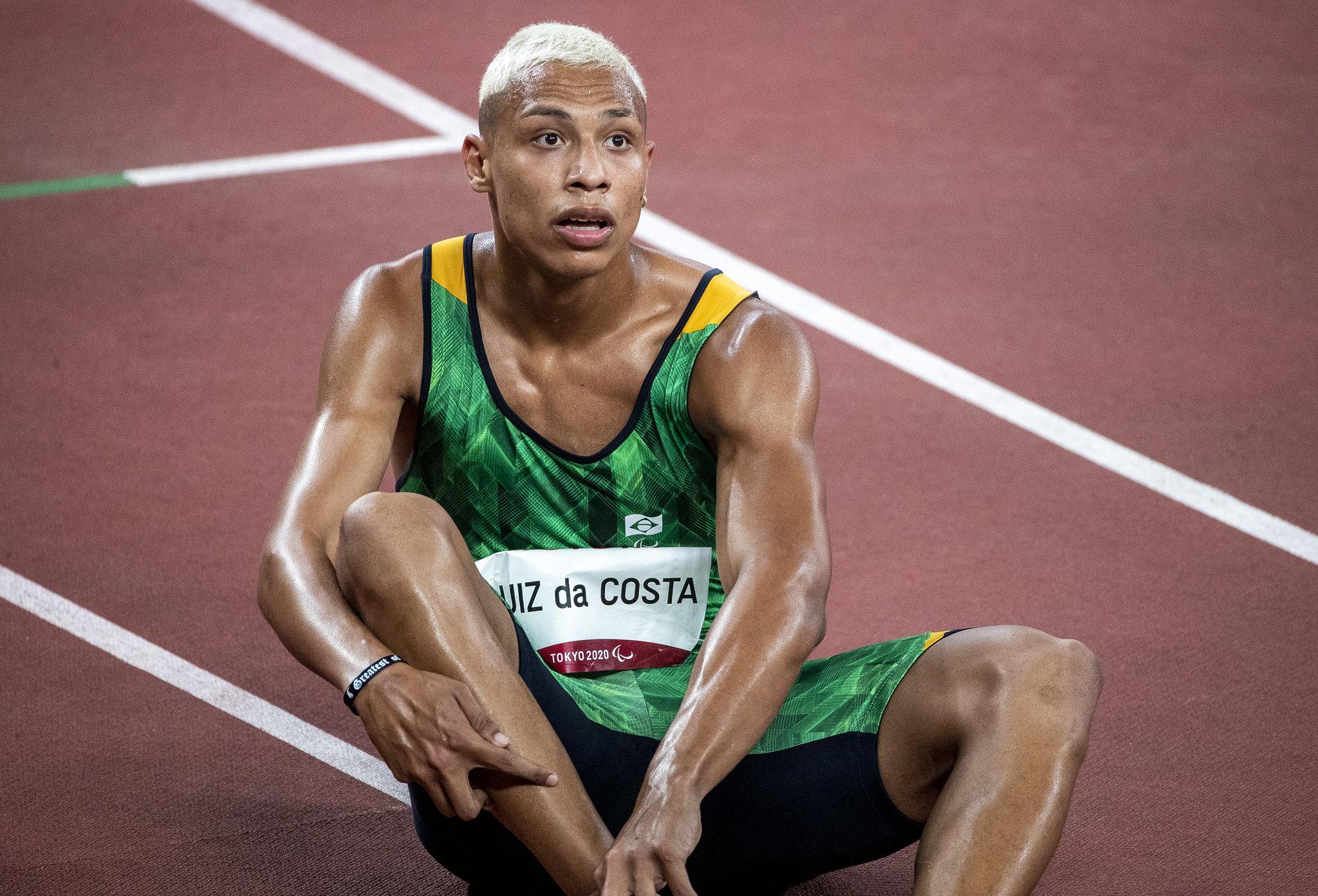 Christian é um rapaz negro, loiro e está sentado na pista de atletismo de Tóquio após uma corrida.