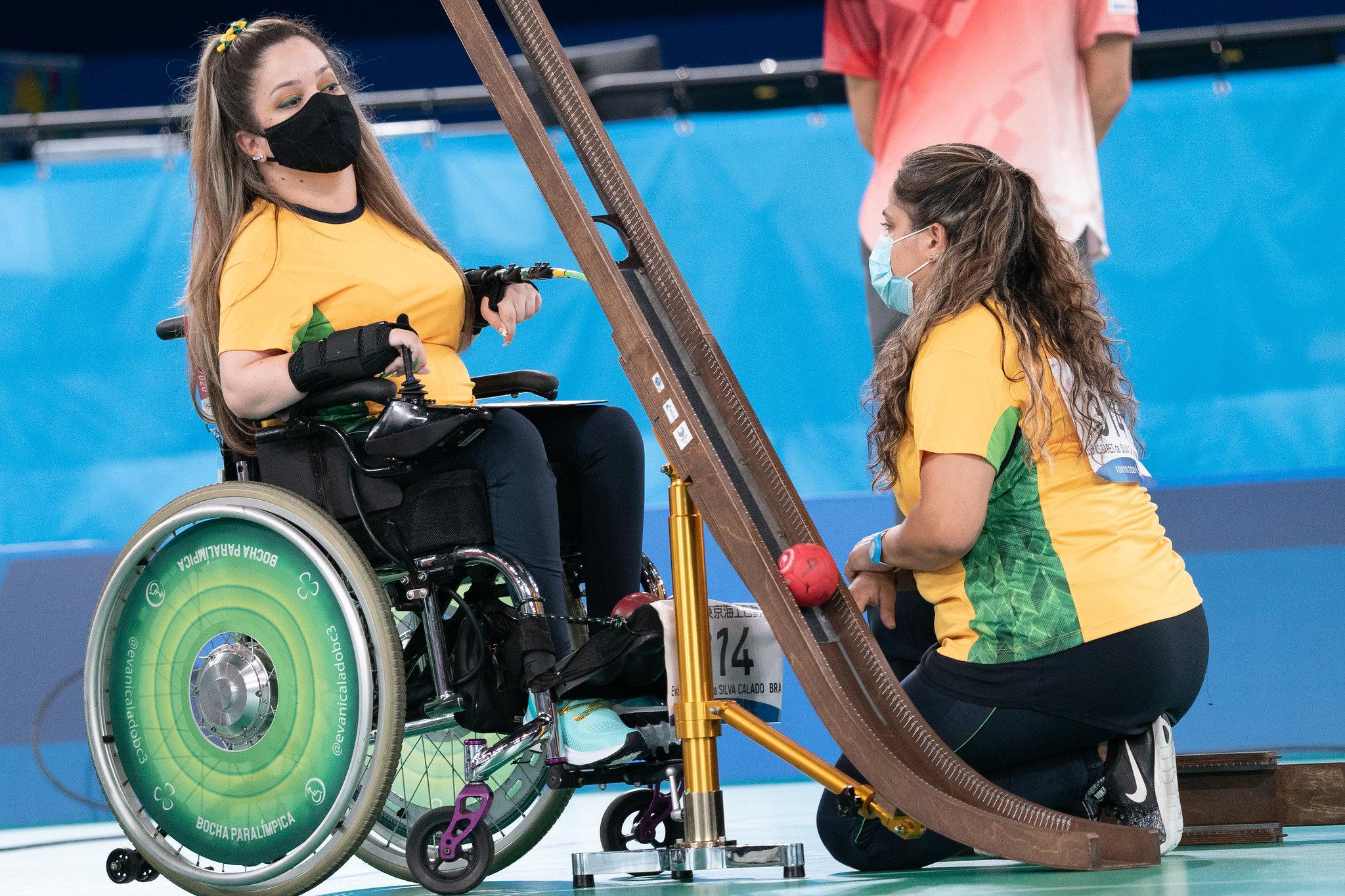 Foto que mostra Evani, na cadeira de rodas, com a camisa da seleção brasileira, de máscara e diante de uma calha, instrumento usado para arremar a bola da bocha. Ela está na frente de sua guia, que está ajoealhada.