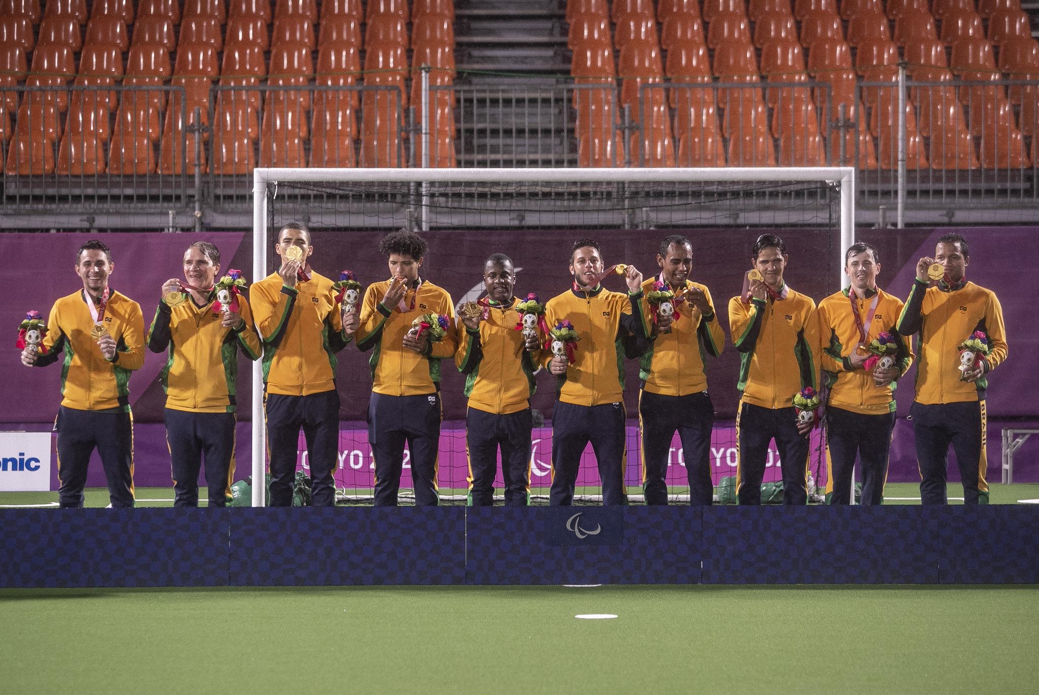 Imagem do time de futebol de 5 no pódio após receber medalha