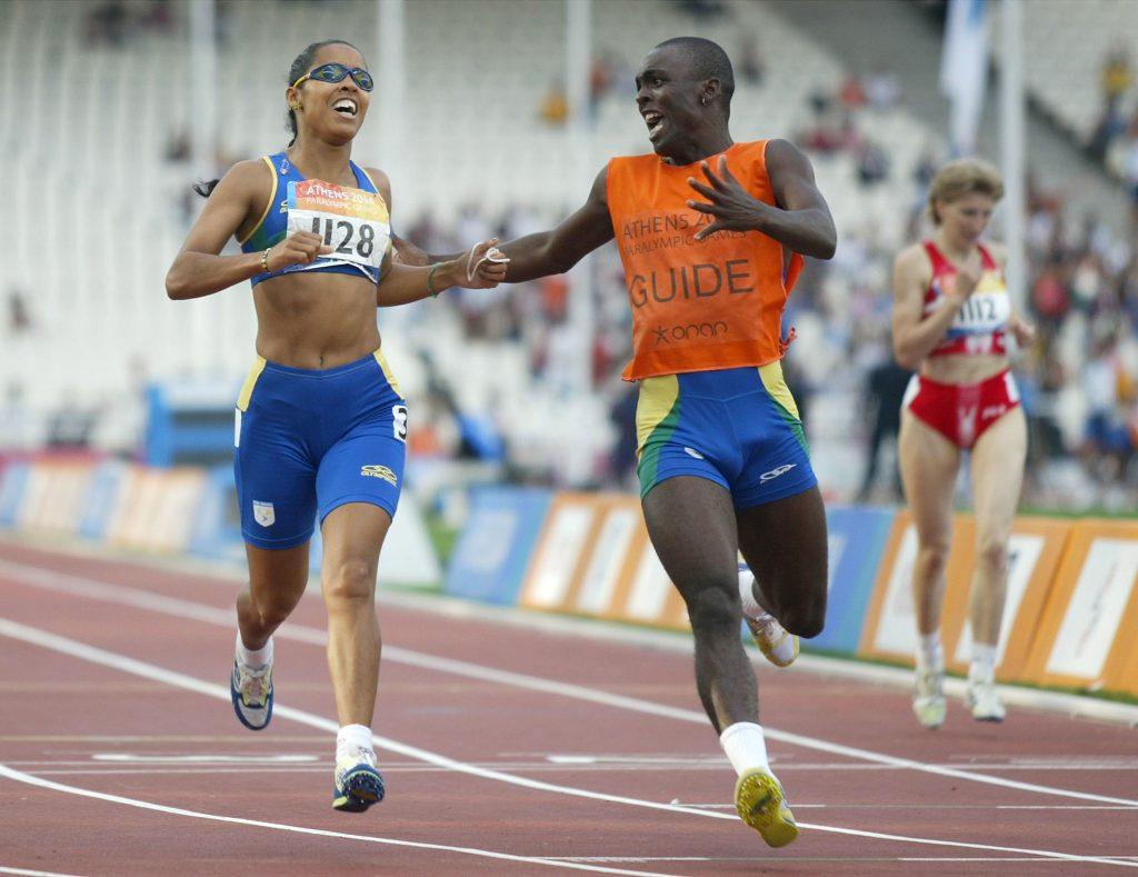 Foto de 2004 que aparece Adria e seu guia Chocolate correndo em uma pista de atletismo. Eles estão sorrindo emocionados.