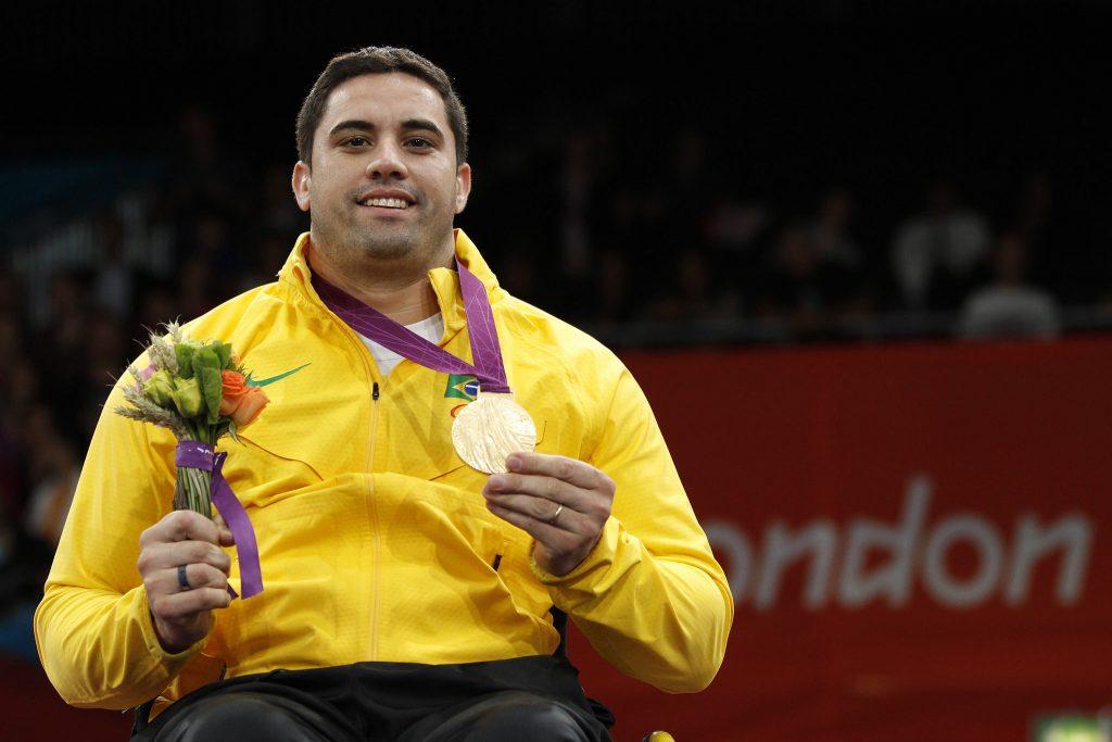 Homem branco de cabelo castanho preto, usando um agasalho todo amarelo representando o Brasil, em uma mão segurando a medalha de ouro conquistada, e um ramo flores na outra simbolizando a honra dos jogos paralímpicos.