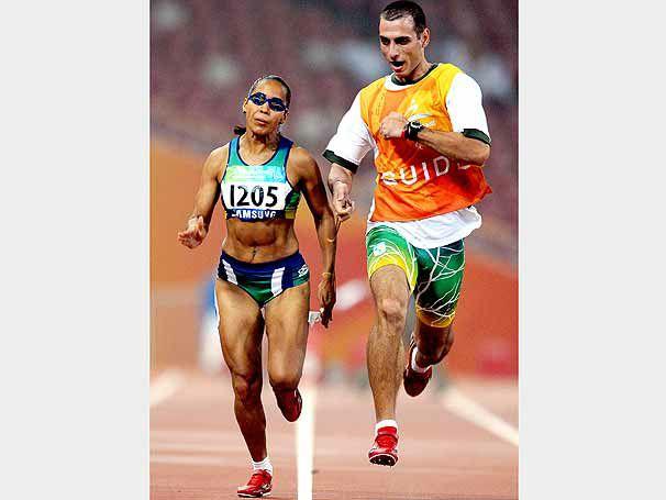 na imagem Adria - a esquerda - corre de frente , em uma pista de atletismo, acompanhada pelo atleta guia - a direita. Ela tem a pele parda, cabelos escuros e presos. Veste um top e shorts curto.