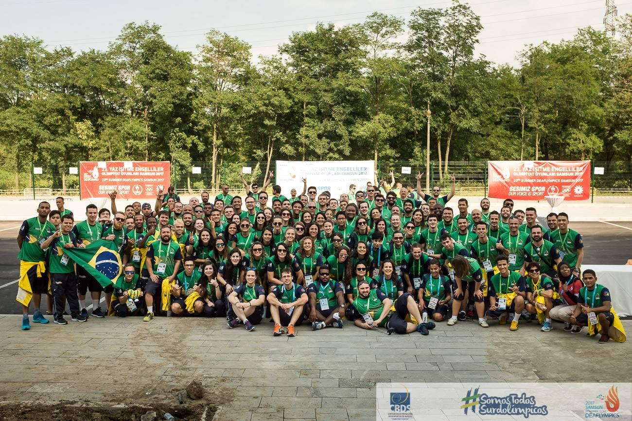 Foto oficial da delegação brasileira de surdoatletas, mais de 50 pessoas, com roupas verde e amarelo.