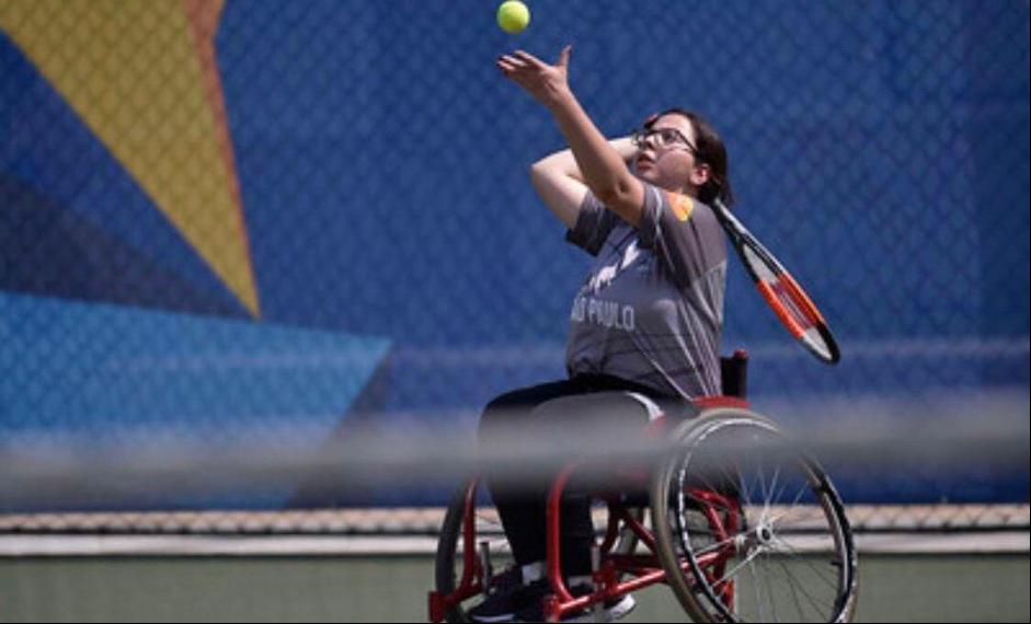 Foto de Fernanda, mulher branca, cabelos curtos, castanhos, olhos da mesma cor. Ela esta sentada em sua cadeira, que possui detalhes vermelhos e pretos, jogando tênis em uma quadra, ela está neste momento jogando a bola para o saque.