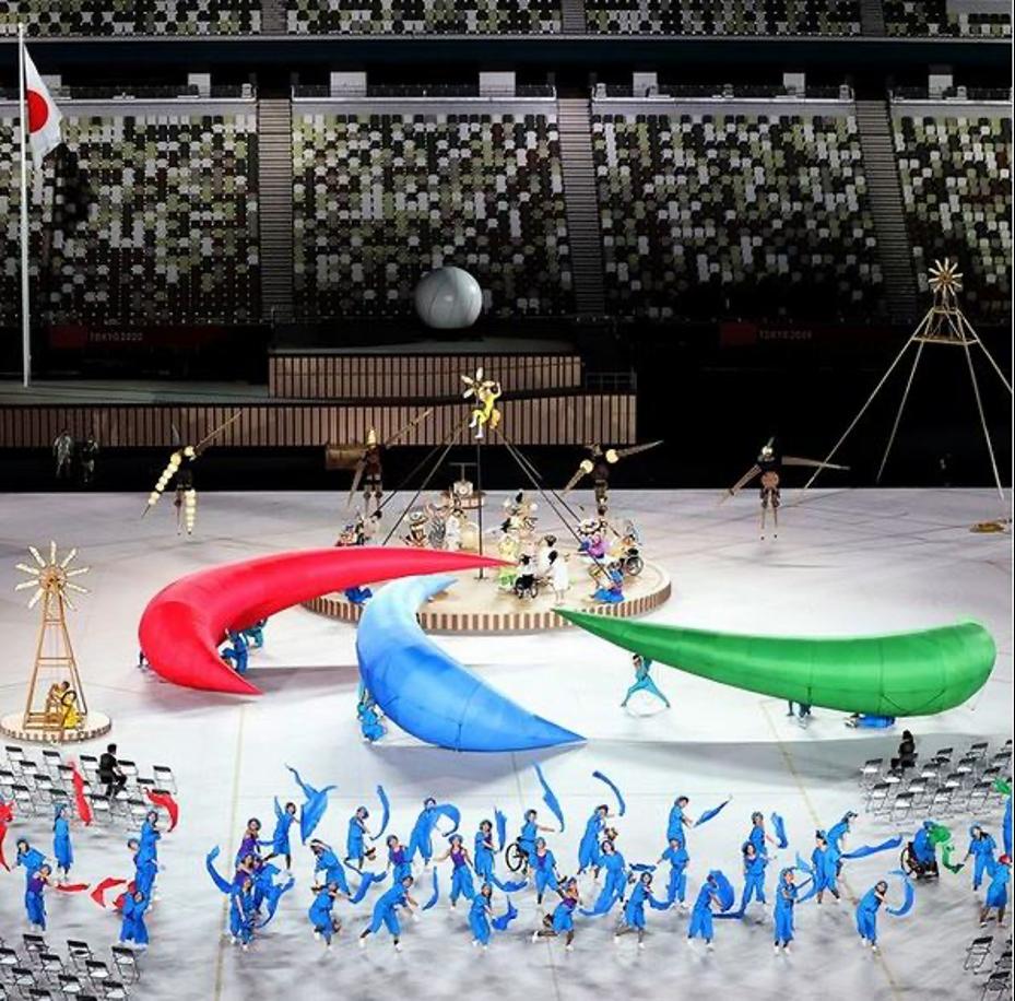 """foto da cerimônia de abertura da Paralimpíada onde está mostrando uma performance artística feita por várias pessoas. No centro do palco, os artistas carregam três arcos de espuma em vermelho, verde e azul que juntos formam o """"Agitos"""", símbolo paralimpíco."""
